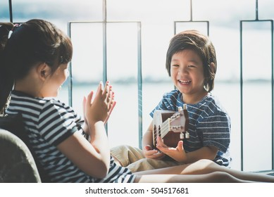 Asian children playing ukulele together near the window