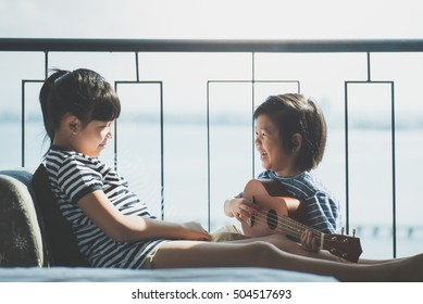 Asian children playing ukulele together near the window