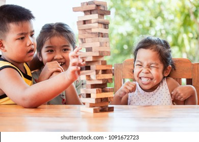 Asian children playing wood blocks stack game together with fun and excited when it falling