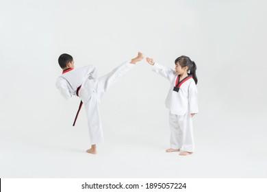 Asian children practicing taekwondo in white studio