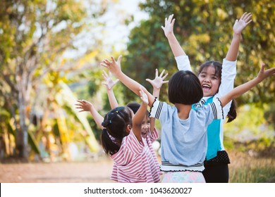 Asian children raise hands and playing together with fun in the park