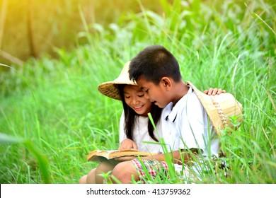 Asian children reading a book in corn field