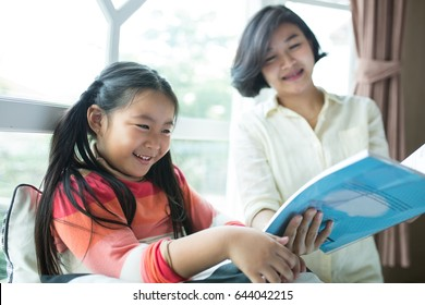 Asian Children reading book with her mother in living room.