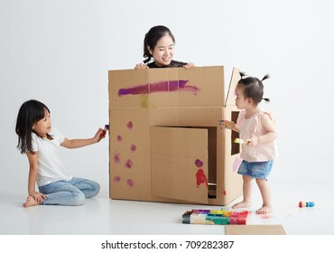Asian children sister with her mother were painting,drawing on the house made of paper. STEAM theme education