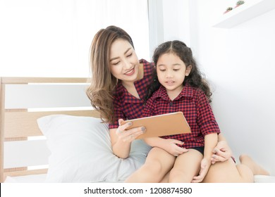 asian children sitting on mother lab, they looking tablet computer in bedroom, they smiling and feeling happy, family time