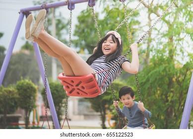 asian children swinging on the playground