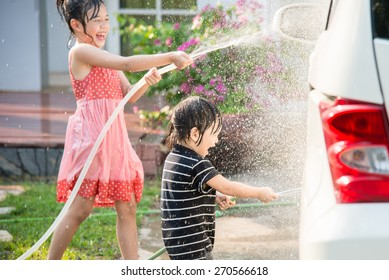 Asian children washing car in the garden