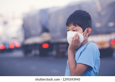 Asian children wearing mask N95 Prevent dust mask PM2.5, toxic fumes, toxic gases, carbon dioxide, in city with blured cars background.
