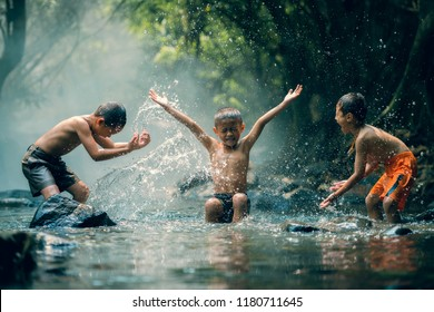 Asian childrens splashing in the river