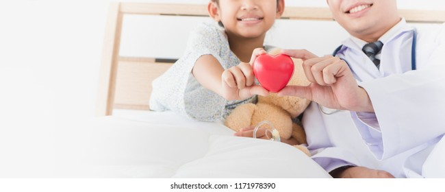 Asian Child's hand and male doctor hold red heart Lying on bed in the hospital.Concept of health care and love in hospitals.