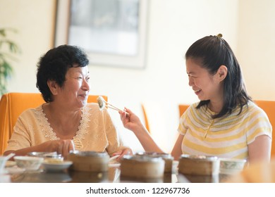 Asian Chinese adult daughter feeding her senior parent food