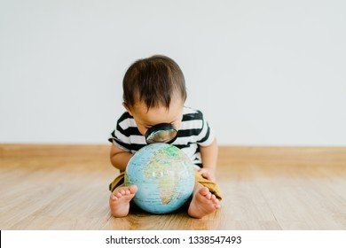 Asian chinese baby boy Looking At Globe Through Magnifying Glass at home on white Background.Concept for research global warming, global network,SEO search engine and Kid Education.