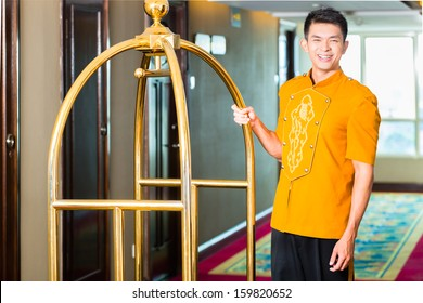 Asian Chinese baggage porter or bell boy or page bringing the suitcase of guests with a box van to the hotel room