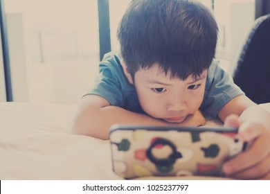 Asian Chinese boy playing smartphone on bed. watching smartphone. kid use phone and play game. child use mobile. addicted game and cartoon