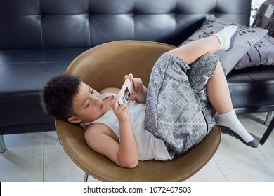 Asian Chinese boy playing smartphone on chair. watching smartphone. kid use phone and play game. child use mobile. addicted game and cartoon
