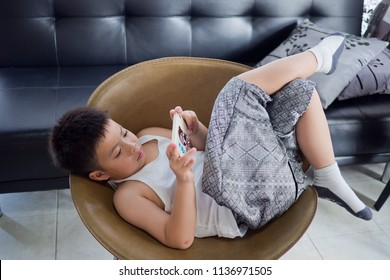 Asian Chinese boy playing smartphone on bed, watching smartphone, kid use phone and play game, child use mobile, addicted game, boy play phone