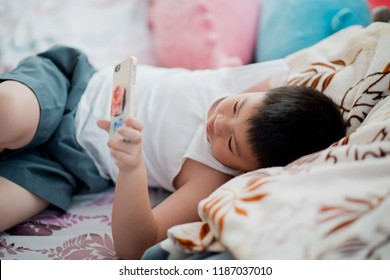asian chinese boy playing smartphone on bed, watching smartphone, kid use phone and play game, child use mobile, addicted game and cartoon, boy play phone