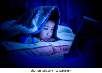 asian chinese boy playing smartphone on bed, watching smartphone, kid use phone and play game, child use mobile, addicted game and cartoon,