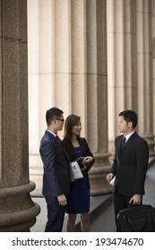Asian or Chinese business colleagues. Professional Lawyer or business team outside a Colonial building.