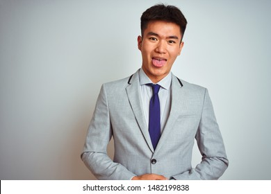 Asian chinese businessman wearing grey jacket and tie standing over isolated white background sticking tongue out happy with funny expression. Emotion concept.