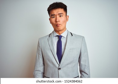 Asian chinese businessman wearing suit and tie standing over isolated yellow background making fish face with lips, crazy and comical gesture. Funny expression.