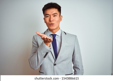 Asian chinese businessman wearing suit and tie standing over isolated yellow background looking at the camera blowing a kiss with hand on air being lovely and sexy. Love expression.