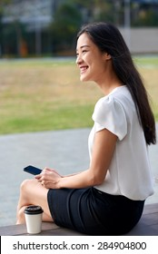 asian chinese businesswoman office worker communicating with mobile phone on coffee break outdoors