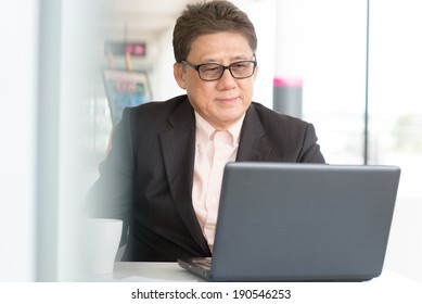 Asian Chinese CEO boss using internet with laptop at cafe. Senior male businessman.