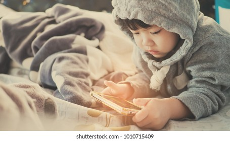 asian  chinese child girl play tablet on bed. kid use telephone.  watching smartphone. watching cartoon. child play phone