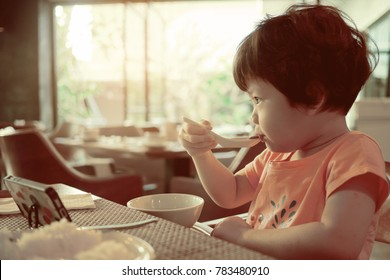 asian  chinese child playing smartphone and eating. children watching cartoon. kid use phone