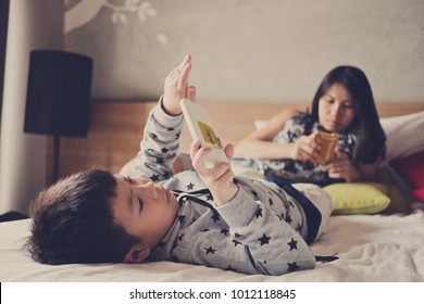 asian  chinese children playing tablet with mother on bed .  chinese child addicted phone. asian boy playing smartphone. kid use telephone. watching smartphone