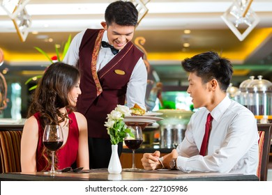Asian Chinese couple - Man and woman - or lovers having a date or romantic dinner in a fancy restaurant while the waiter is serving food