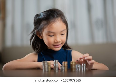 Asian Chinese girl counting coins, stacking them up