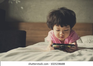 Asian Chinese girl playing smartphone on bed. watching smartphone. kid use phone and play game. child use mobile. addicted game and cartoon