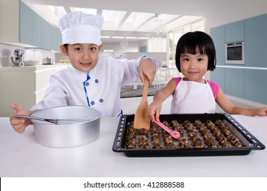 Asian Chinese Kid Baking Cookies against Kitchen Background