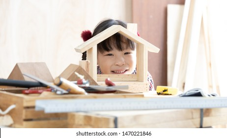 Asian Chinese kid girl carpenter working on wood working table in home carpentry shop, Little asian kid girl works in home business carpentry shop, Authentic asian girl.