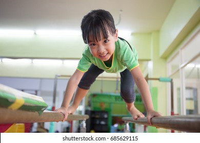 Asian Chinese little girl climbing on parallel bars at indoor playground