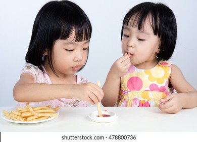Asian Chinese little girl Eating French Fries  indoor with isolated clean background.