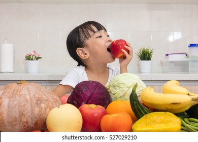 Asian Chinese little girl eating apple in front fruit and vegetable in the kitchen at home.