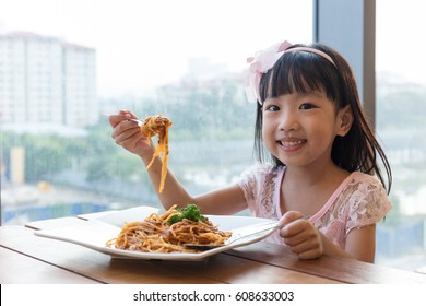Asian Chinese little girl eating spaghetti bolognese in the restaurant.