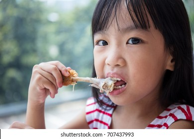 Asian Chinese little girl eating fried chicken at indoor restaurant