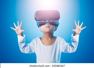 Asian Chinese little girl experiencing virtual reality eyeglassses in isolated background.