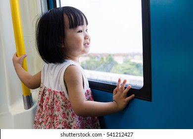 Asian Chinese little girl inside a MRT transit looking far way beside the window.