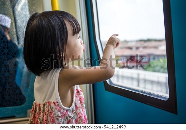 Asian Chinese little girl inside a MRT transit looking far way beside the window.