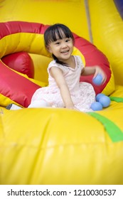 Asian Chinese little Girl Playing with Balls at Indoor Playground