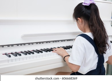 Asian Chinese little girl playing classical piano in the living room at home