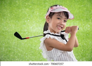 Asian Chinese little girl playing golf on green grass