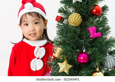 Asian Chinese little girl posing with Christmas Tree on plain white background studio.
