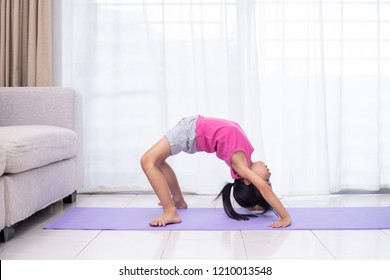 Asian Chinese little girl practicing yoga pose on a mat in the living room at home