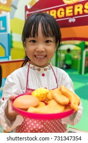 Asian Chinese little girl role-playing at burger store at indoor playground